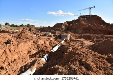 Laying concrete manholes and drain pipes for stormwater system. Connecting a trench drain to a concrete manhole structure at construction site. Construct stormwater and underground utilities