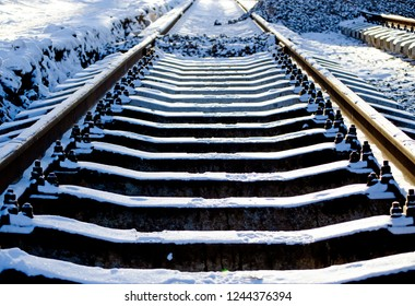 Laying the construction of new tram rails, snowy weather, rails and sleepers stretching into the distance covered with snow