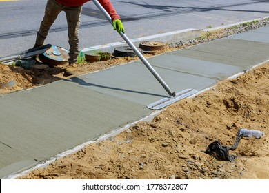 Laying down new sidewalk in wet concrete on freshly poured sidewalks - Shutterstock ID 1778372807