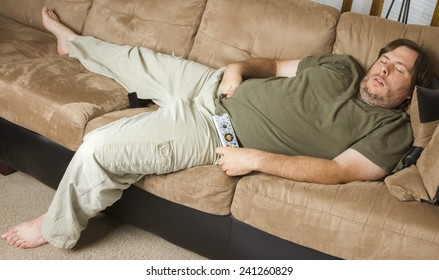 laying down on the couch with his hands down his pants a fat man is asleep