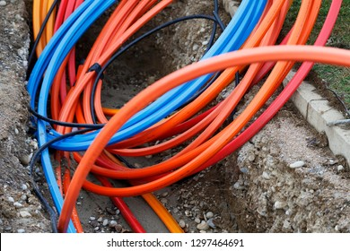 Ein Glasfaserkabel für schnelles Internet, Strom und Telefonkabel entlang einer neuen Straße. Kabel-Installations-Stromleitungen in der Stadtstraße, Industrie-Elektrizität und Kommunikation Konzept.