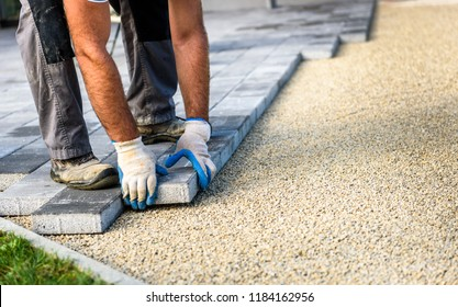 Laying gray concrete paving slabs in house courtyard driveway patio. Professional workers bricklayers are installing new tiles or slabs for driveway, sidewalk or patio on leveled sand foundation base.