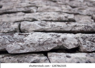 The laying of gray natural stones of asymmetric rectangular shape on the roof of the Trulli house in Alberobello, close-up