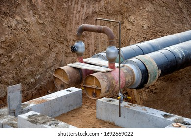 Laying heating pipes in a trench at construction site. Installation underground storm system of water main and sanitary sewer. Ground water drainage pipe