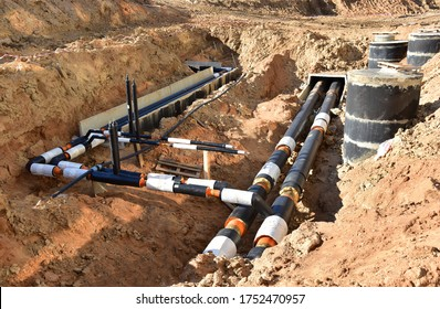 Laying heating pipes in trench at construction site. Installing concrete sewer wells and underground storm systems of sanitary water main. Cold and hot water heating system of the apartments in house
