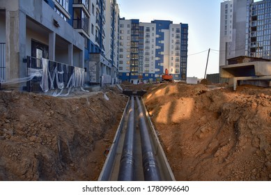Laying heating pipes in a trench at construction site. Install underground storm systems of water main and sanitary sewer. Cold and hot water, heating and heating system of apartments in the house