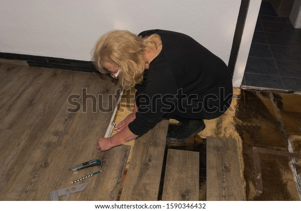 Laying laminate or parquet in the room, worker laying wood or linoleum laminate on the floor and marking the laminate length