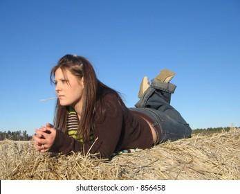 Laying on hay roll, in thought.