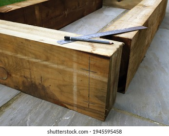 Laying out and measuring up railway sleepers for DIY construction project with steel ruler and pencil . Raised flower beds or trough, or planter. Domestic back garden. Outdoors on a bright spring day.