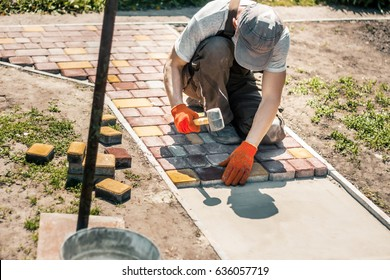 Laying Paving Slabs by mosaic close-up. Road Paving, construction. Repairing sidewalk. Worker laying stone paving slab. Laying colored tiles in city park (garden). Hand fixed tessellated sidewalk tile