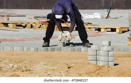 laying paving slabs on city square, repairing sidewalk