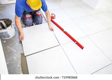 Laying tiles at home. Construction worker laid floor tiles.