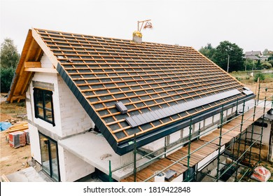 laying tiles on the roof of a single-family house