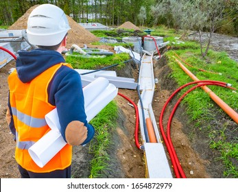Laying utilities. Man looks at the pipes leading to the well. Builder with drawings next to the water supply. Pipes at the construction site lead. Human in a construction uniform looks at water pipes