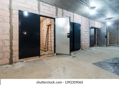 Layout of building materials bricks. unfinished, incomplete, pending. Monolithic brick basement wall. heating pipes lie on floor. New empty room. Сonstruction stage of residential monolithic house.