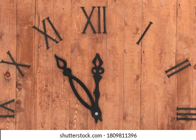 Layout clock. Dial with Roman numerals. Textured brown planks wood base. Black hands of the clock show the time - five minutes to twelve. New Year holiday concept.