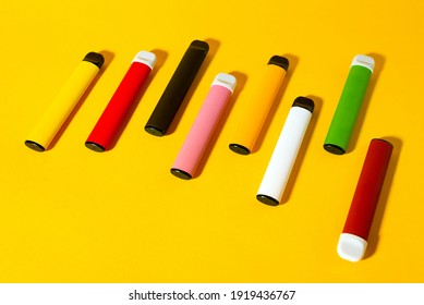 Layout of colorful disposable electronic cigarettes with shadows on a yellow background. The concept of modern smoking, vaping and nicotine. Top view