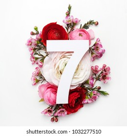 Layout with colorful flowers, leaves and number seven. Flat lay. Top view.