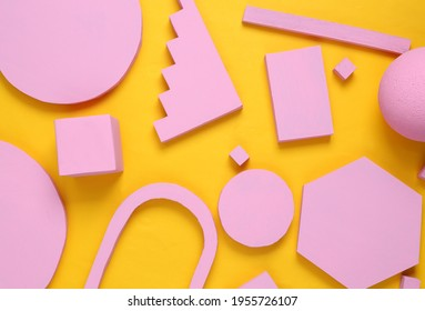 Layout composition of pink geometric shapes on yellow background. Flat lay
