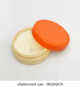 Layout cream jars with colorful lid on a white background
