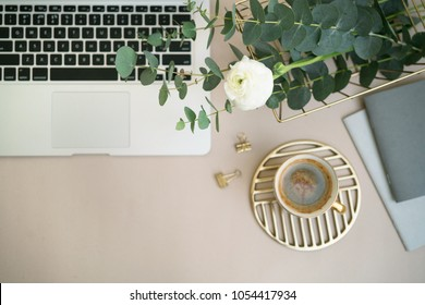 Layout of desk with laptop keyboard, coffee cup and flowers, notebook,  eucalyptus in basket. Top view, copy space for text. Woman's study or work accessories on the pastel table.