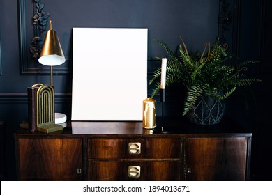 layout of the photo frame in a modern stylish interior, designer accessories table lamp and book holder. a golden candle and green house plants on a vintage wooden table.