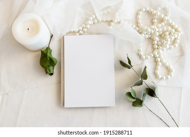 Layout scene of a stationery layout. An empty vertical greeting card, a string of pearls and dried flowers isolated on a white table background. Top view blank for invitation