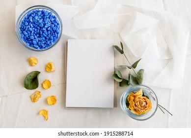Escena de diseño de un diseño de diseño de papel. Una tarjeta vertical de saludo vacía, una cadena de perlas y flores secas aisladas en un fondo de mesa blanca. Vista superior en blanco para invitación