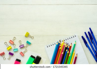 Layout of school supplies on a white wooden background
