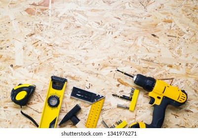 The layout of the yellow tools on the OSB: screwdriver, hammer, level, angle, rutelka, bits.