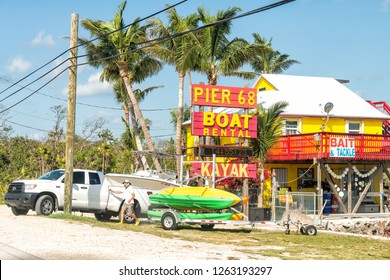 Layton, USA - May 1, 2018: Sign for Pier 68 rental, kayak, bait and tackle services, shop, store in Florida Long key at overseas highway road, street, palm trees, man, truck picking boat on trailer
