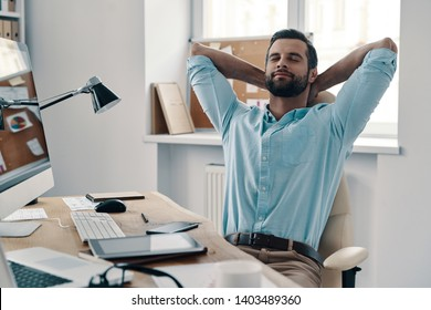 Laziness. Young modern businessman keeping hands behind head and smiling while sitting in the office