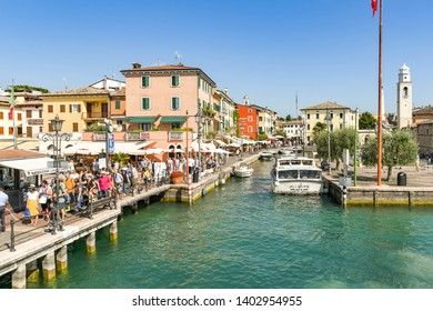LAZISE, LAKE GARDA, ITALY - SEPTEMBER 2018:  The entrance to the harbour in Lazise on Lake Garda. On the left, visitors are queuing to catch one of the ferries which call at the town