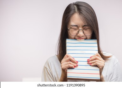 Lazy Asian student female wearing spectacles, biting a book, unwilling to study, isolated shot at studio over white background with copyspace.