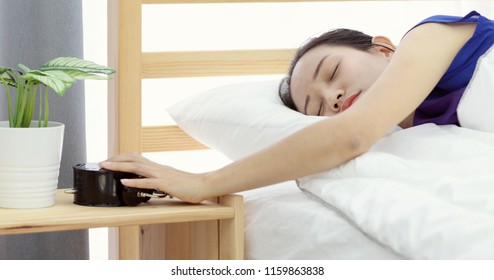 lazy asian woman refusing to wake up lying on her bed