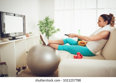 Lazy beautiful young woman in sport clothing sitting front of the TV and doesn't wont to exercise.