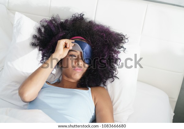 Lazy black girl with blindfold in bed late in the morning. Tired African American woman with sleeping mask sleeping during daytime.