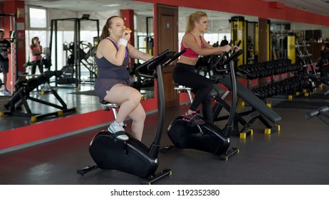 Lazy corpulent woman eating bun and riding stationary bike in gym, fitness