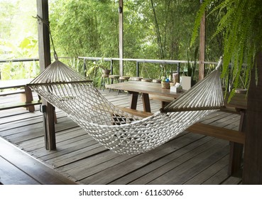 The lazy cot on the wooden balcony with solid wood dining table