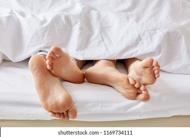 Lazy day concept. Wifes and husbands bare feet from white blanket. Female and male stay in bed, focus on legs, enjoy weekend and togetherness, sleep for long time. People, rest and relax concept