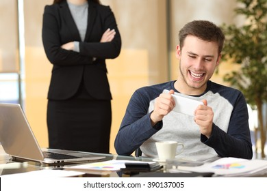 Lazy employee playing games with his smartphone sitting in a desktop while his angry boss is watching at office