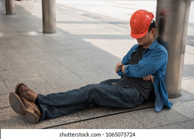 Lazy engineer with orange helmet sleeping at construction site in modern city. Engineering man take a nap to rest and relax after hard working.