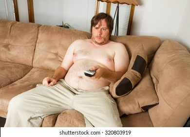 Lazy fat man watching Tv while on the couch