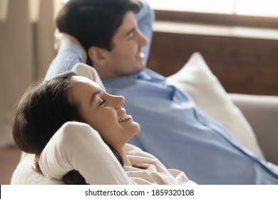 Lazy leisure. Smiling content young husband and wife resting relaxing at home leaning back on cozy sofa at living room having pleasure breathing fresh air dreaming with closed eyes meditating together