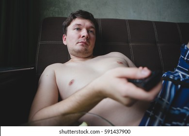 Lazy man with beer and chips watching TV at home