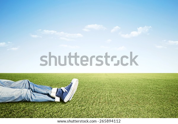 Lazy man lying on the grass doing nothing