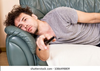 Lazy man with the remote on the couch
