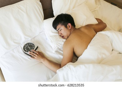 Lazy man sleeping and wake up late in the morning on his bed with copy space