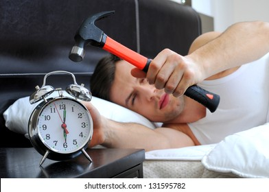Lazy man is smashing the alarm clock with a hammer from the bed