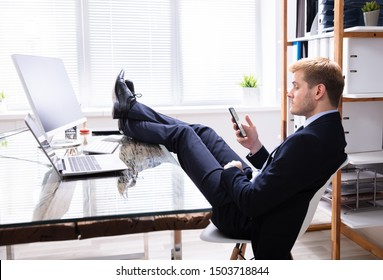 Lazy Man Using Phone At Work Desk Instead Of Working